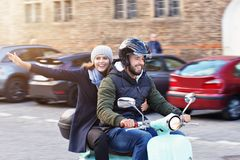 Beautiful young couple smiling while riding scooter in city in autumn stock photo