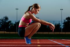 Picture of beautiful young European female runner or sprinter sitting on outdoor stadium track, feeling exhausted after Stock Images