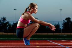 Picture of beautiful young European female runner or sprinter sitting on outdoor stadium track, feeling exhausted after Royalty Free Stock Photos