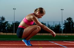 Picture of beautiful young European female runner or sprinter sitting on outdoor stadium track, feeling exhausted after Stock Photography