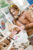 Picture of beautiful young woman holding a white basket in her hands looking happy smiling in supermarket or department store Royalty Free Stock Photography