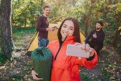 Picture of beautiful young woman takes selfie and smiles. She holds sleeping bag. Young men on back poses as well. They royalty free stock photo