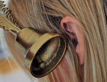 A picture of a bell next to an ear stock image