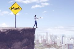 Blindfolded businesswoman with bitcoin word. Picture of blindfolded businessman walking on the cliff with bitcoin word on a signpost Stock Photo