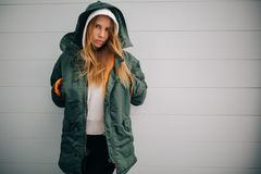 Picture of blond model in hood and in jacket against gray wall. Background Royalty Free Stock Photo