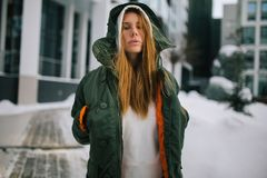 Picture of blond model in hood and in jacket against winter day. Building background Royalty Free Stock Photos