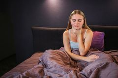 Picture of blonde sits on bed and holds one hand on throat. She has sore there. Model keeps eyes closed. She is alone in royalty free stock photography