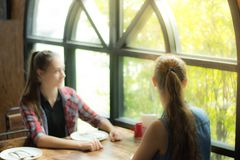 Picture blurred for background two young woman sitting at the table waiting for her meal.Smiling girl looking out of the window. Stock Photo