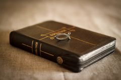 Picture of a book Bible close-up in black leather binding with a zipper with a Christian pendant symbol fish on a gray background.  Royalty Free Stock Photo