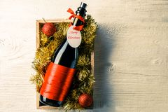 Picture of bottle of wine with card in box with tinsel Royalty Free Stock Photos