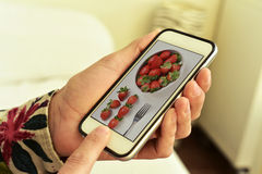 Picture of a bowl with strawberries in a smartphone Royalty Free Stock Photos
