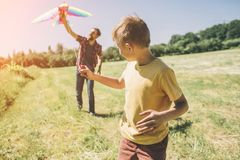 A picture of boy running and looking back. He is holding kite on thread. Father is helping him to run the kite to the. Sky royalty free stock photography