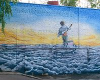 Picture on a brick wall (graffiti), depicting a boy standing with a paddle boat, floating on the waves to the solar horizon Stock Photos