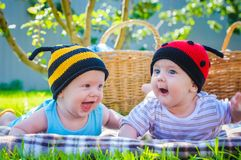Little girl in knitted ladybird hat and boy playing outdoors, best friends, happy family, love and happiness concept royalty free stock photography