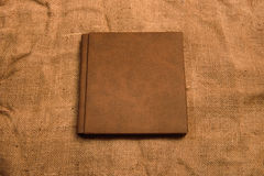 Picture of brown leather photo album cover on jute background. K Royalty Free Stock Images