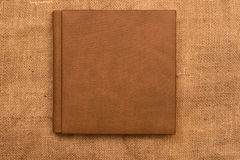Picture of brown leather photo album cover on jute background. K Stock Photography
