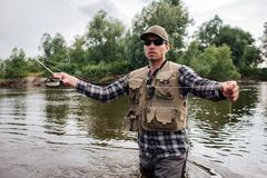 A picture of brutal and calm guy standing in water and looking forward. He has fly rod in one hand and spoon from it in