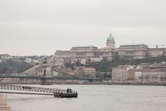 Buda Castle seen from Pest with the Danube in front. The cast is the historical palace complex of the Hungarian kings. Picture of Buda Castle during a grey Royalty Free Stock Photos