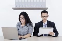 Business couple working together in the office. Picture of a business couple working with a laptop and tablet while sitting together in the office Royalty Free Stock Images