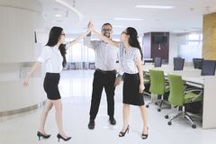 Business people giving high five hands at office. Picture of business people celebrating their success by giving high five hands together in the office Royalty Free Stock Photo