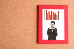 Picture of business woman in frame with graph on wooden table Stock Photo