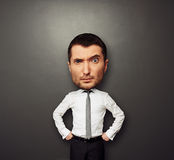 Picture of businessman with big head. Funny picture of businessman with big head over dark background Royalty Free Stock Photography