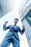 Businessman stands between skyscrapers and makes a winners fist Royalty Free Stock Image