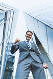 Businessman stands between skyscrapers and makes a winners fist Stock Photography