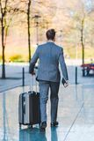 Businessman walks with a trolley bag in the city. Picture of a businessman who walks with a trolley bag in the city Stock Photo