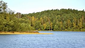 Calm lake in the forest during an early autumn color change.