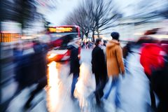 People crossing a city street at dusk Royalty Free Stock Photo