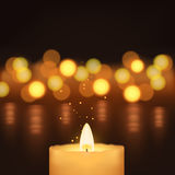 Picture of candles. Illustration of one burning candle in front of some lights Stock Image