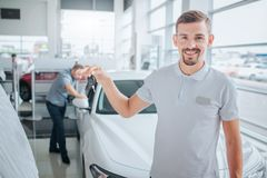 Picture of car deeler stands and looks on camera. He smiles and holds car key. Potential purchaser stands and leans on royalty free stock photo