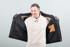 Picture of casual stylish man with pullover and jacket. Smiling on gray studio background Royalty Free Stock Images