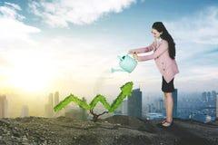 Caucasian businesswoman watering upward arrow royalty free stock photo