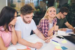 Picture of cheerful young blonde woman look on camer and smile. Other students work on their projects at table. They are. Picture of cheerful young blonde women stock image