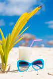 Picture chilled cocktail and blue sunglasses on tropical beach near small palm tree Royalty Free Stock Photos