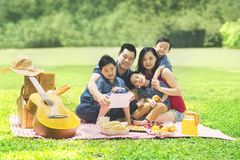 Chinese family using a tablet in the park. Picture of Chinese family using a digital tablet while picnicking in the park Stock Photos