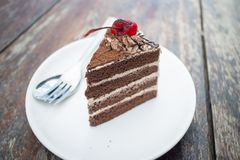 Chocolate cake with cherry topping in cozy outdoor cafe stock photo