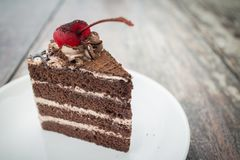 Chocolate cake with cherry topping in cozy outdoor cafe royalty free stock photos