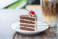 Chocolate cake with cherry topping and ice coffee mocha in outdoor cafe. Picture of chocolate cake with cherry topping and ice coffee mocha in outdoor cafe royalty free stock photos