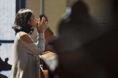 Christian Asian woman prays in the church stock image