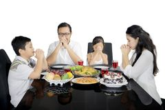 Christian family praying before having dinner on studio Royalty Free Stock Photos