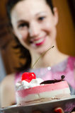 Picture close up on delicious slice of cake with cherry and cream & beautiful young woman brunette girl on the background. Closeup image of delicious slice of Stock Image