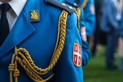 Close up on the coat of Arms of the Serbian army on a soldiers formal uniform during a ceremony in the Belgrade French Embassy. Royalty Free Stock Images