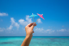 Picture of cocktail umbrella on the tropical beach, vacation. Tr. Aveller dreams concept Stock Photos