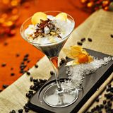 Coffee cocktail with cream and grated ice. A picture of a coffee cocktail with a topping of cream and grated ice, with a tiny tuft of whipped cream and some Royalty Free Stock Images