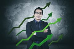 Confident businessman with growth statistic. Picture of confident businessman smiling at the camera while standing with arrows upward of finance statistic Royalty Free Stock Images