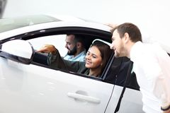 Confident young salesman explaining car features to the young attractive owners. Picture of confident young salesman explaining all the car features to the young royalty free stock images