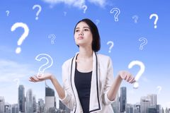 Confused businesswoman with question marks Stock Image